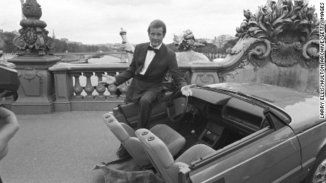 British actor Roger Moore on set of the James Bond movie 'A View to a Kill' with half a car during filming in Paris, France in August 1984. (Photo by Larry Ellis/Express/Getty Images)