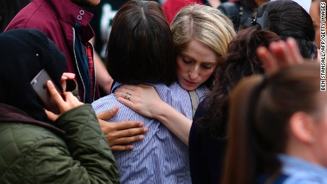 TOPSHOT - Retail staff hug each other after being evacuated from the Arndale Centre shopping mall in Manchester, northwest England on May 23, 2017 following a security alert the day after a deadly terror attack at the Manchester Arena.   Twenty two people have been killed and dozens injured in Britain's deadliest terror attack in over a decade after a suspected suicide bomber targeted fans leaving a concert of US singer Ariana Grande in Manchester. / AFP PHOTO / Ben STANSALL        (Photo credit should read BEN STANSALL/AFP/Getty Images)