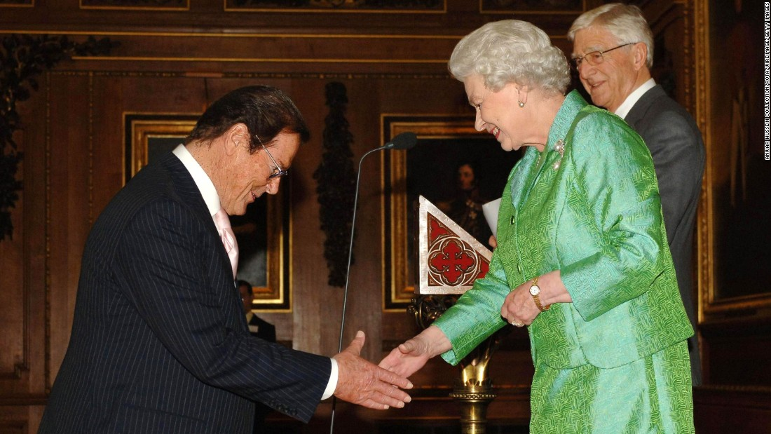 Moore is greeted by Britain's Queen Elizabeth II at Windsor Castle in 2006. In 2003, he was knighted for his charity work.