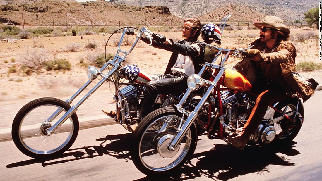 """This is the Captain America Motorcycle designed by Ben Harvey and Clifford Vaughn -- two motorcycle customization people working during the 1960s in LA. They made the bike for Easy Rider and Peter Fonda (left.) We have a replica of the bike in the show as the original was destroyed in the movie."""
