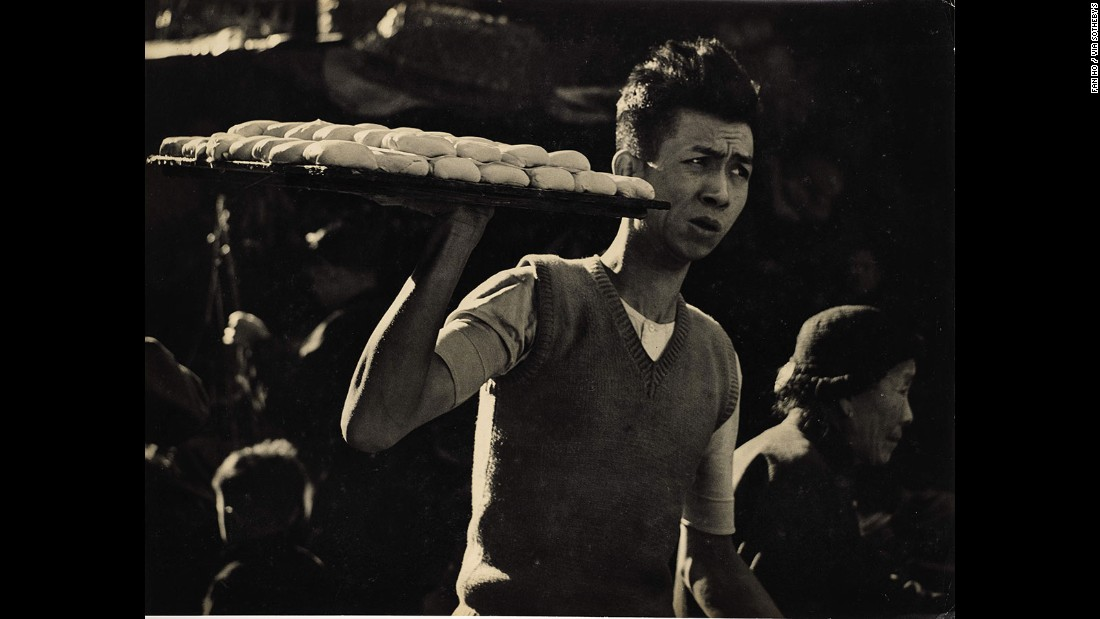 A young man carries a tray of tofu through the Hong Kong's streets