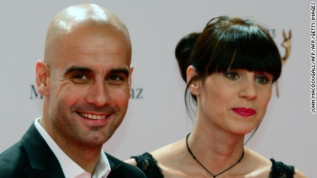 Bayern Munich's Spanish head coach Pep Guardiola (L) and his wife Christina pose for photographers on the red carpet as they arrive for the Bambi awards at the Stage theatre at Potsdamer Platz in Berlin on November 14, 2103. The awards ceremony ubder the patronage of German publisher Hubert Burda and awards nominees in the sectors of communication, entertainment and show business as well as economy, politics and sports. AFP PHOTO / JOHN MACDOUGALL        (Photo credit should read JOHN MACDOUGALL/AFP/Getty Images)