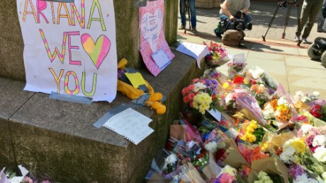 Flowers and posters of support are left in St Ann's square in tribute to the concert victims.