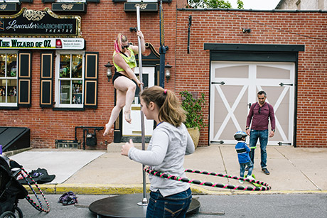 Rachel Syke, 33, does a pole dancing exercise demonstration during Open Streets in Lancaster, Pennsylvania. Open Streets encourages residents to be outside and meet other people in the community.