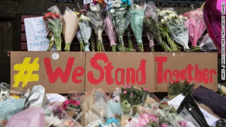 "Floral tributes and a message that reads ""We Stand Together"" are pictured in Albert Square in Manchester, northwest England on May 24, 2017, left as tributes to the victims of the May 22 terror attack at the Manchester Arena. Police on Tuesday named Salman Abedi -- reportedly British-born of Libyan descent -- as the suspect behind a suicide bombing that ripped into young fans at an Ariana Grande concert at the Manchester Arena on May 22, as the Islamic State group claimed responsibility for the carnage. / AFP PHOTO / CHRIS J RATCLIFFE        (Photo credit should read CHRIS J RATCLIFFE/AFP/Getty Images)"