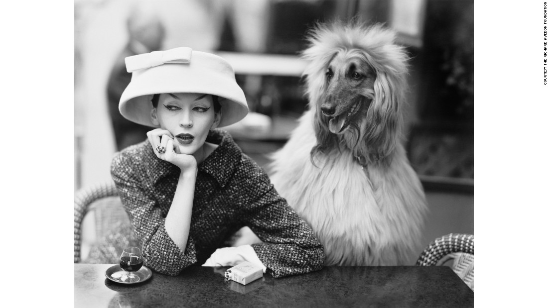 Model Dovima (left) wears a cloche and suit by Balenciaga at the Café des Deux Magots in Paris in 1955.