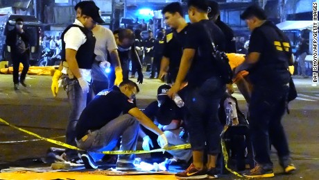 Indonesian police investigators check a body part found after a suicide bomb blast at Kampung Melayu bus terminal in Jakarta on May 24, 2017.