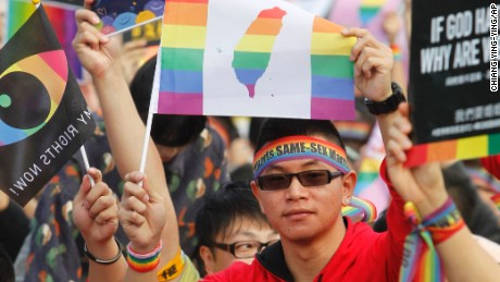 A supporter of LGBT and human rights holds a rainbow flag with Taiwan map during a rally supporting a proposal to allow same-sex marriage in Taipei, Taiwan, Saturday, Dec. 10, 2016. Tens of thousands of supporters hold a gathering to support same-sex marriage and coincide on the World Human Rights Day. They hope the bill to allow same-sex marriage would be able to passed before the end of this year. (AP Photo/Chiang Ying-ying)