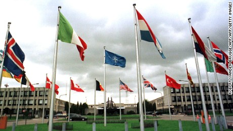 "BRUSSELS, BELGIUM - OCTOBER 12:  Dark clouds hang over NATO members' flags outside the alliance's headquarters in Brussels, 12 October. The NATO allies were poised today to vote a critical ""activation order"" to attack Yugoslavia, as US envoy Richard Holbrooke pressed 11th-hour talks in Belgrade with a recalcitrant President Slobodan Milosevic to avert war in the Balkans.  (Photo credit should read ROBERT VANDEN BRUGGE/AFP/Getty Images)"