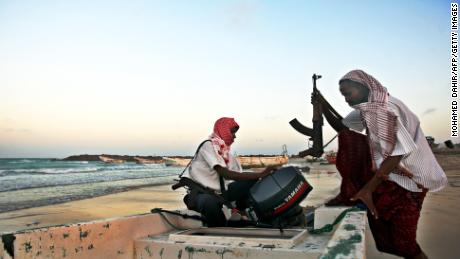 Photo taken on January 4, 2010 shows armed Somali pirates carrying out preparations to a skiff in Hobyo, northeastern Somalia, ahead of new attacks on ships sailing in the Gulf of Aden. Greek cargo ship, MV Filitsa, is anchored just off the shores of Hobyo where it is held by pirates with its crew of 22, including three Greek officers and 19 Filipinos, after being captured some 513 nautical miles northeast of the Seychelles while sailing from Kuwait to Durban in South Africa loaded with fertilizer.     AFP PHOTO / MOHAMED DAHIR (Photo credit should read MOHAMED DAHIR/AFP/Getty Images)