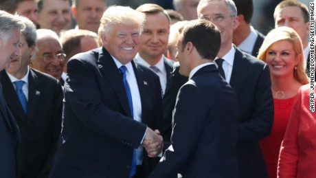 RESTRICTED U.S. President Donald Trump, center left, shakes hands with Emmanuel Macron, France's president, as other world leaders look on during a summit of world leaders at the North Atlantic Treaty Organization (NATO) in Brussels, Belgium, on Thursday, May 25, 2017. U.S. President Donald Trump's demands to step up the fight against terrorism are set to resonate with his NATO partners when he visits the alliance headquarters for the first time on Thursday. Photographer: Jasper Juinen/Bloomberg via Getty Images
