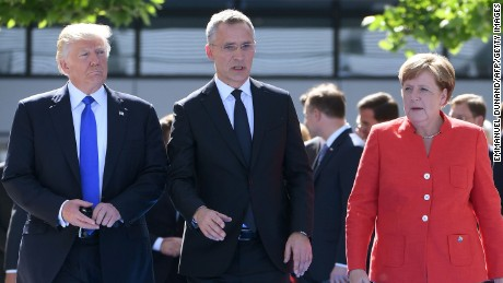 NATO Secretary General Jens Stoltenberg (C) speaks with US President Donald Trump (L) and  German Chancellor Angela Merkel (R) as they arrive for the unveiling ceremony of the Berlin Wall monument, during the NATO (North Atlantic Treaty Organization) summit at the NATO headquarters, in Brussels, on May 25, 2017. / AFP PHOTO / Emmanuel DUNAND        (Photo credit should read EMMANUEL DUNAND/AFP/Getty Images)
