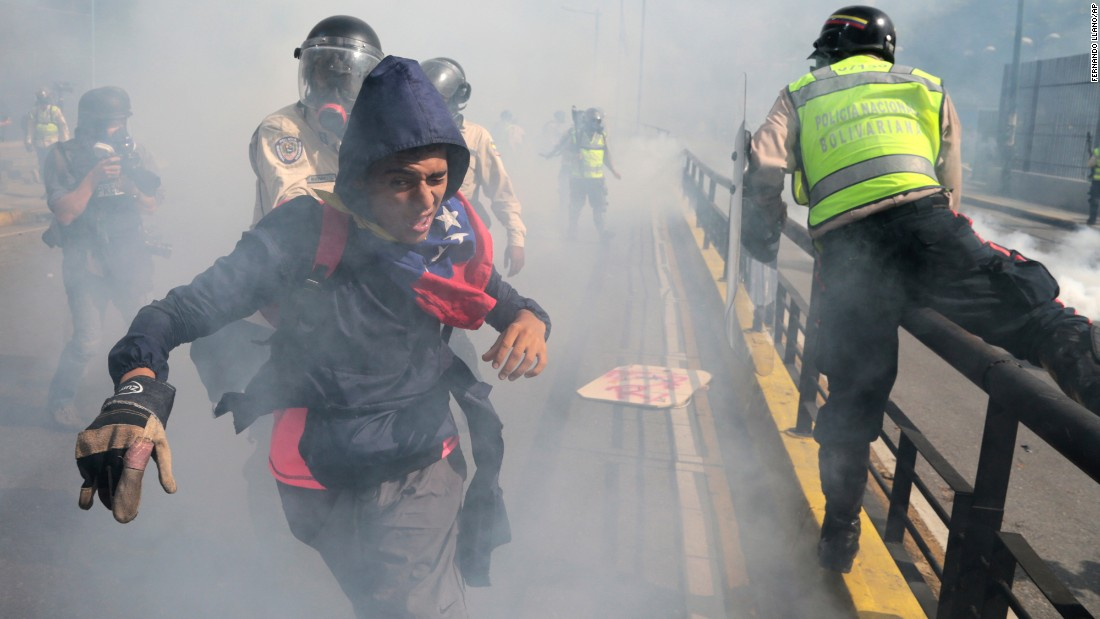 "A protester tries to flee from government security forces during a demonstration in Caracas, Venezuela, on Saturday, May 20. Hundreds marched along Caracas' Francisco Fajardo highway, one of the city's major routes, while some flanked a gigantic sign that read ""Elections Now"" over an overpass. It was the country's <a href=""http://www.cnn.com/2017/05/21/americas/venezuela-50-day-protests/"" target=""_blank"">50th consecutive day</a> of anti-government protests."