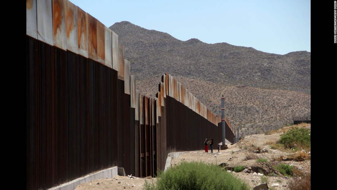 A Mexican family stands next to the US border wall in Ciudad Juarez, Mexico, on Tuesday, May 23. The United States is about to complete the construction of a metal wall, nearly 23 feet high, on the border between Ciudad Juarez and El Paso, Texas. It replaces a wire-mesh fence that was built in 1986, officials said.