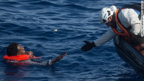 LAMPEDUSA, ITALY - MAY 24: A rescue crewmember from the Migrant Offshore Aid Station (MOAS) 'Phoenix' vessel reaches out to pull a man into a rescue craft after a wooden boat bound for Italy carrying more than 500 people partially capsized on May 24, 2017 off Lampedusa, Italy. The Migrant Offshore Aid Station (MOAS) 'Phoenix' vessel rescued 603 people after one of three wooden boats partially capsized leaving more than 30 people dead. Numbers of refugees and migrants attempting the dangerous central Mediterranean crossing from Libya to Italy has risen since the same time last year with more than 43,000 people recorded so far in 2017. In an attempt to slow the flow of migrants Italy recently signed a deal with Libya, Chad and Niger outlining a plan to increase border controls and add new reception centers in the African nations, which are key transit points for migrants heading to Italy. MOAS is a Malta based NGO dedicated to providing professional search-and-rescue assistance to refugees and migrants in distress at sea. Since the start of the year MOAS have rescued and assisted 3572 people and are currently patrolling and running rescue operations in international waters off the coast of Libya.  (Photo by Chris McGrath/Getty Images)