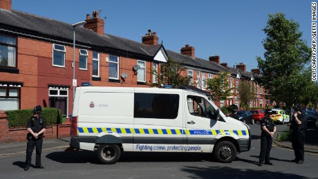 Police officers stand on duty outside the entrance to Dorset Avenue in Moss Side, Manchester, on May 26, 2017, following a raid on a residential property as their investigations continue into the May 22 terror attack at the Manchester Arena.