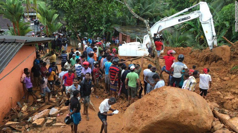 Residents watch a rescue operation in Bellana village after monsoon rains caused landslides in the region.