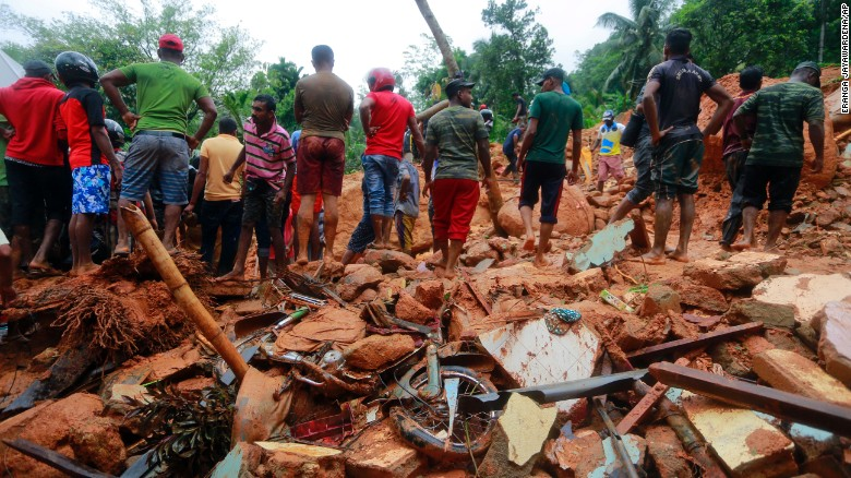 Sri Lankan military rescuers and villagers stand on the debris of a house that was destroyed by a landslide in Bellana village on Friday.
