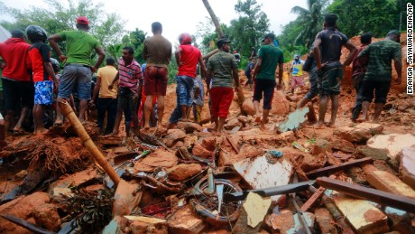 Sri Lankan military rescuers and villagers stand on the debris of a house that was destroyed in a landslide in Bellana village in Kalutara district, Sri Lanka, Friday, May 26, 2017. Mudslides and floods triggered by heavy rains in Sri Lanka killed more than a dozen people with four others missing, Home Affairs Minister Vajira Abeywardana said Friday. (AP Photo/Eranga Jayawardena)