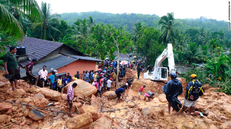 Residents of Bellana village in the Kalutara district watch as heavy machinery tries to move landslide debris on Friday, May 26, 2017