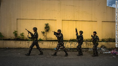 MARAWI CITY, PHILIPPINES - MAY 25: Soldiers take positions while evading sniper fire as they try to clear the city of armed militants one street at a time, on May 25, 2017 in Marawi city, southern Philippines. Gun battles between ISIS-linked militants and Filipino troops erupted in Marawi city on Tuesday when gunmen from the local terrorist groups Maute Group and Abu Sayyaf rampaged through the southern city, prompting President Rodrigo Duterte to declare 60 days of martial law in Mindanao. Thousands of residents were reported to have fled from Malawi city while at least 21 people were killed, including a police chief who had been beheaded and buildings were torched by the terror groups. President Duterte said the influence of Islamic State is one of the nation's top security concerns, and martial law on Mindanao island could be extended across the Philippines to enforce order, allowing the detention of people without charge. (Photo by Jes Aznar/Getty Images)