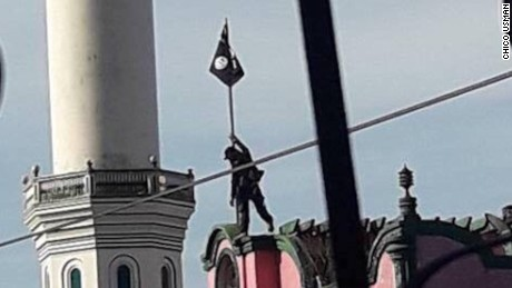 An ISIS fighter erects the flag of the so-called Islamic State atop a school near a mosque in Marawi, southern Philippines on May 24, 2017.
