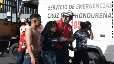 Members of the Red Cross assist an injured supporter of Honduran team Motagua after a stampede at the National Stadium in Tegucigalpa on May 28, 2017. At least two people were killed and 25 injured in the chaos and unrest caused when hundreds of fans tried to enter the overcrowded stadium before the final match of the Clausura football tournament between Motagua and Honduras Progreso. / AFP PHOTO / ORLANDO SIERRA