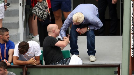 Agassi (left) speaks with Boris Becker -- Djokovic's former coach -- on day two at Roland Garros