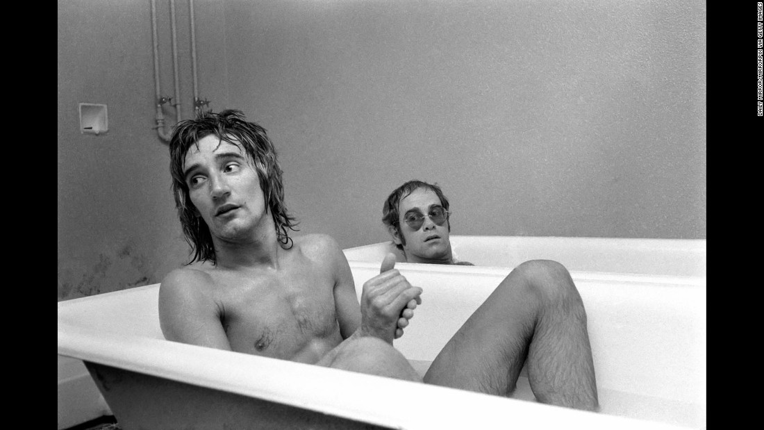 John and singer Rod Stewart have a bath at the stadium of Watford Football Club in 1973. John, a lifelong Watford fan, later owned the English soccer club. Today, one of the stadium's stands is named after him.