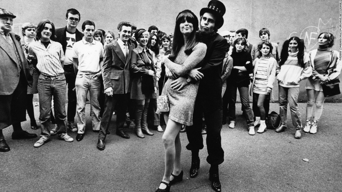"Fans watch John embrace singer and friend Kiki Dee in 1978. The two had a No. 1 hit, ""Don't Go Breaking My Heart,"" in 1976."