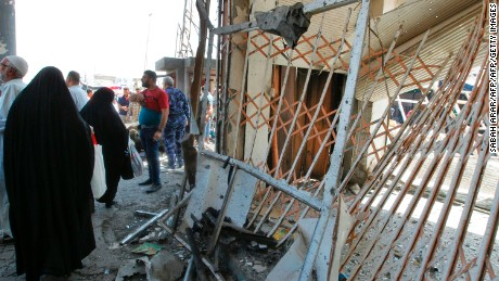 Iraqis gather at the site of a car bomb explosion near Baghdad's General Retirement Department.