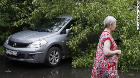 A woman walks past a fallen tree on a car after a heavy storm in Moscow.