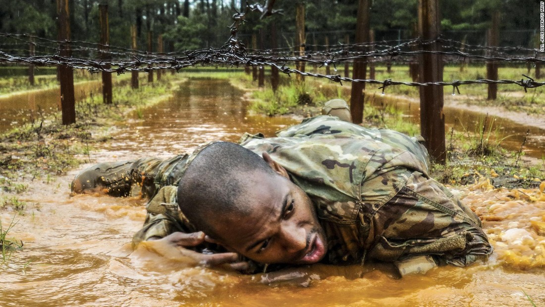 "A paratrooper crawls under barbed wire during a ""best squad"" competition in Fort Bragg, North Carolina, on Tuesday, May 23. It was part of All-American Week, which celebrated the Army's 82nd Airborne Division."