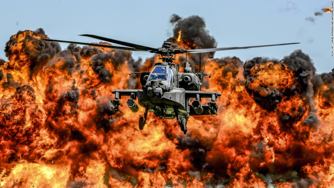 An AH-64D Apache attack helicopter flies in front of a wall of fire Saturday, May 6, during the South Carolina National Guard's Air and Ground Expo. The fire was part of the demonstration.