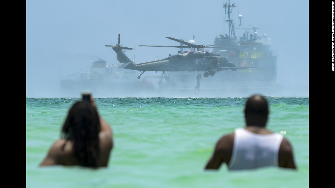 People wade in the water as they watch an air and sea show in Miami Beach, Florida, on Sunday, May 28. The demonstration involved military assets.