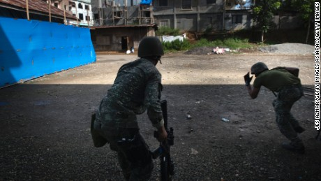 MARAWI CITY, PHILIPPINES - MAY 30: Filipino soldiers engage in a firefight with ISIS-linked militants, on May 30, 2017 in Marawi city, southern Philippines. Philippine government troops are battling their way as they inch towards the city center where ISIS-linked militants have been holed for nearly a week.  The fighting at Marawi city had forced around 85,000 people to seek refuge at evacuation centers in Marawi as the week long gun battles between ISIS-linked militants and security troops rose to around 100 with at least 19 civilians being killed in the fighting, according to local media. Filipino authorities announced around 2,000 people had been stranded amid street battles and air strikes while bodies of foreign Islamist militants were discovered during the ongoing battles in the southern city. President Rodrigo Duterte had declared 60 days of martial law in Mindanao on Tuesday after local terrorist groups Maute Group and Abu Sayyaf rampaged through Marawi city and said that martial law could be extended across the Philippines while thousands of residents continue to flee the crisis in Marawi, which is home to some 200,000 people. Jes Aznar/Getty Images