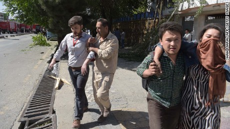 EDITORS NOTE: Graphic content / Afghan men (2nd L and 2nd R) provide assistance to the wounded at the site of a car bomb attack in Kabul on May 31, 2017.
