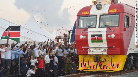 People cheer and throw confetti, after Kenyan President Uhuru Kenyatta flags off a cargo train for its inaugural journey to Nairobi, at the port of the coastal town of Mombasa on May 30, 2017. More than a century after a colonial railway gave birth to modern Kenya, the country is betting on a new Chinese-built route to cement its position as the gateway to East Africa. The $3.2 billion (2.8 billion euro) railway linking Nairobi with the port city of Mombasa will May 31 take its first passengers on the 472 kilometre (293 mile) journey, allowing them to skip a hair-raising drive on one of Kenya's most dangerous highways.  / AFP PHOTO / TONY KARUMBA        (Photo credit should read TONY KARUMBA/AFP/Getty Images)