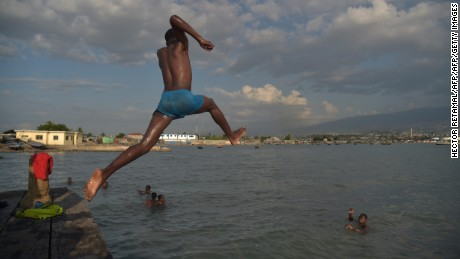 A youth leaps into the sea during sunset while playing with friends at the wharf Soleil, in the commune of Cite Soleil, in the capital of Haiti, Port-au-Prince, on May 4, 2017. / AFP PHOTO / HECTOR RETAMAL        (Photo credit should read HECTOR RETAMAL/AFP/Getty Images)
