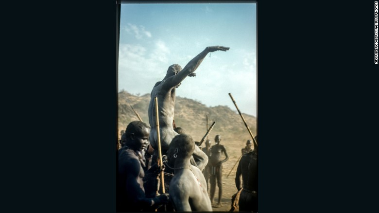 A victorious Nuba wrestler held aloft by his defeated competition. Until now, Rodger's Sudan pictures had only been published in monochrome.
