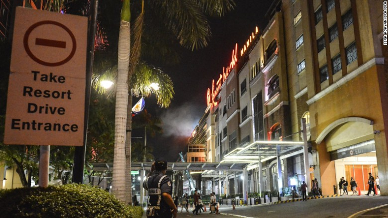 A police officer stands guard outside Resorts World Manila, a popular tourist site in the Philippines that was on lockdown after a shooting. A police official said the incident was a robbery attempt by one person and not a terrorist attack.
