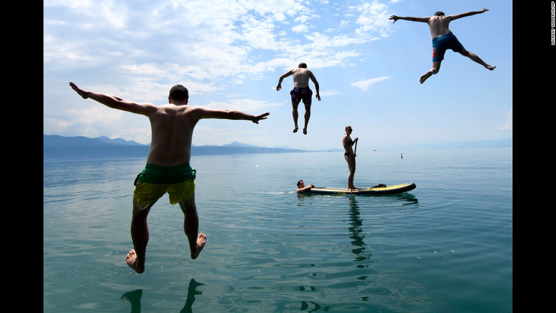 Men jump into Lake Geneva in Lutry, Switzerland, on Monday, May 29.