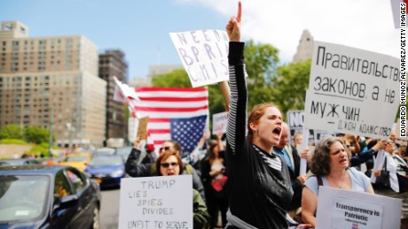 "Demonstrators take part in an anti-Trump ""March for Truth"" rally at Foley Square on June 3, 2017 in New York City. The sign in Russian reads, ""Government of Laws, not men"" - John Adams."