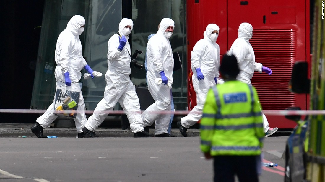 A group of police forensic officers walks in the street outside Borough Market.