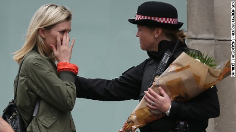 A woman reacts after asking a Police officer to lay flowers near London Bridge.