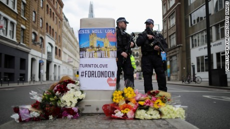 Armed police stand guard in front of floral tributes on Southwark Street near the scene of last night's terrorist attack on June 4, in London, England.