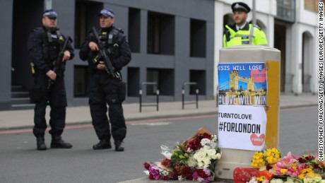 LONDON, ENGLAND - JUNE 04:  Armed police stand guard in front of floral tributes on Southwark Street near the scene of last night's terrorist attack on June 4, 2017 in London, England. Police continue to cordon off an area after responding to terrorist attacks on London Bridge and Borough Market where 7 people were killed and at least 48 injured last night. Three attackers were shot dead by armed police.  (Photo by Christopher Furlong/Getty Images)