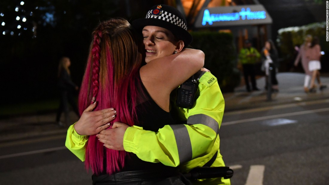 A music fan hugs a police officer as fans leave Old Trafford Cricket Ground after the benefit concert for the families of the victims of the May 22, Manchester terror attack.