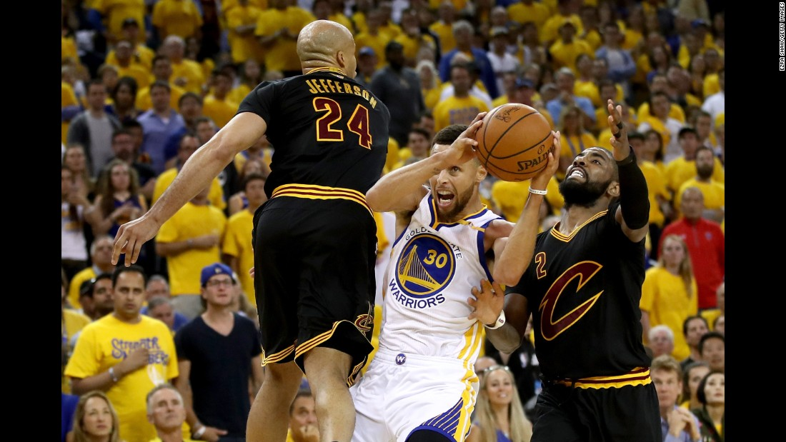 Curry drives to the hoop against Richard Jefferson, left, and Irving.