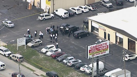 Officers gather in an industrial district of suburban Orlando, where multiple people were killed.